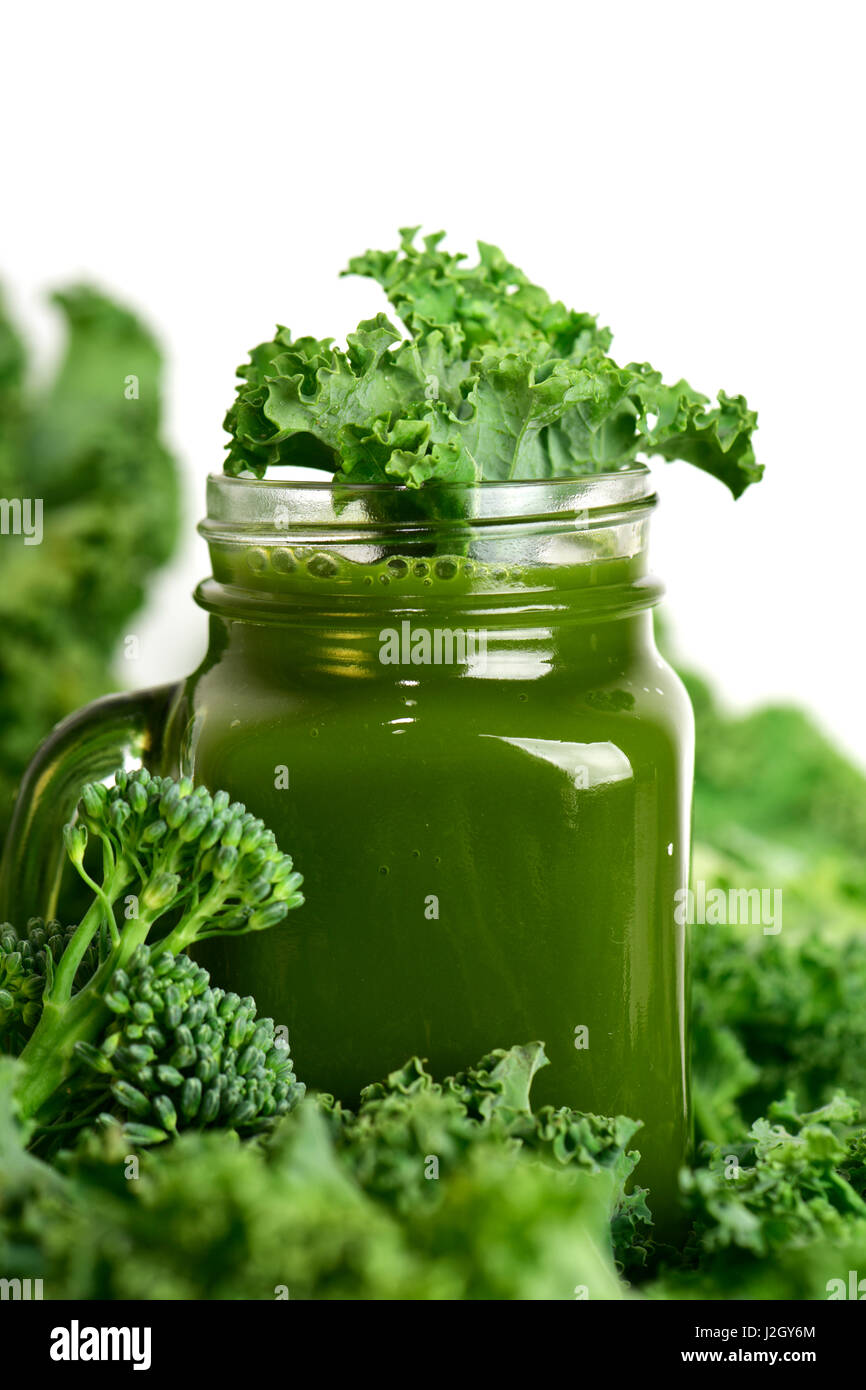 a green smoothie served in a glass mason jar surrounded by some leaves of kale and some stems of broccolini on a - Stock Image