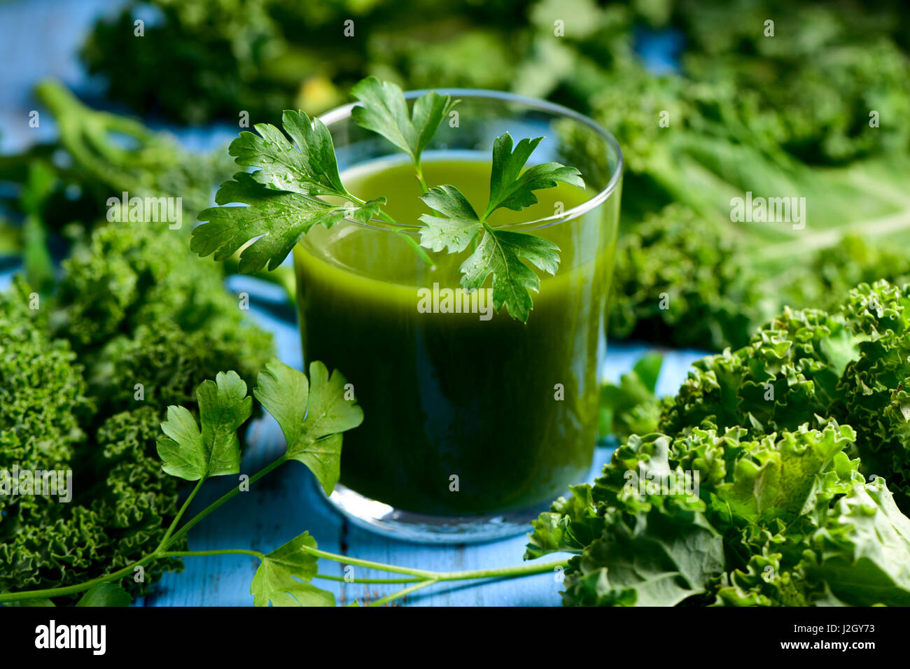 a glass with kale smoothie topped with a twig of parsley and some leaves of kale on a blue rustic wooden table - Stock Image