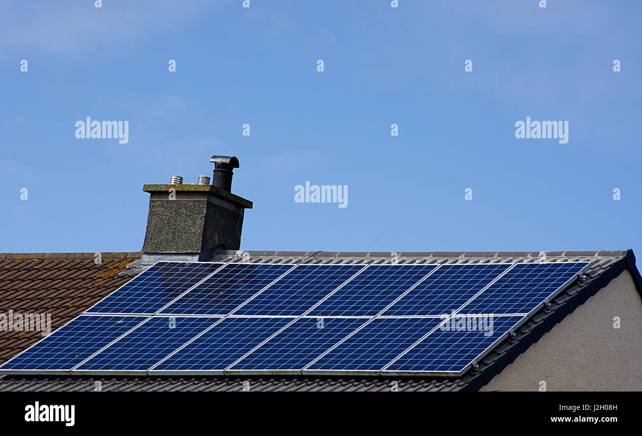 Solar panels on sloped house roof with blue sky in background,North Wales,UK.Energy Uk,renewable energy source.Solar - Stock Image