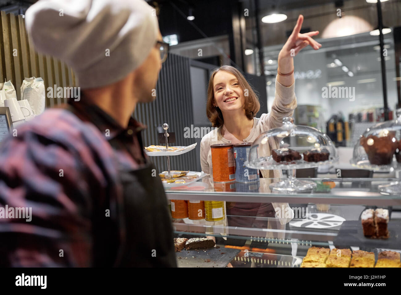 happy woman showing something to bartender at cafe - Stock Image