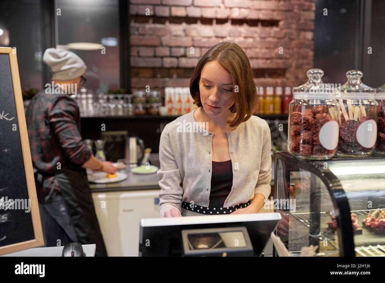 woman or barmaid with cashbox at cafe - Stock Image