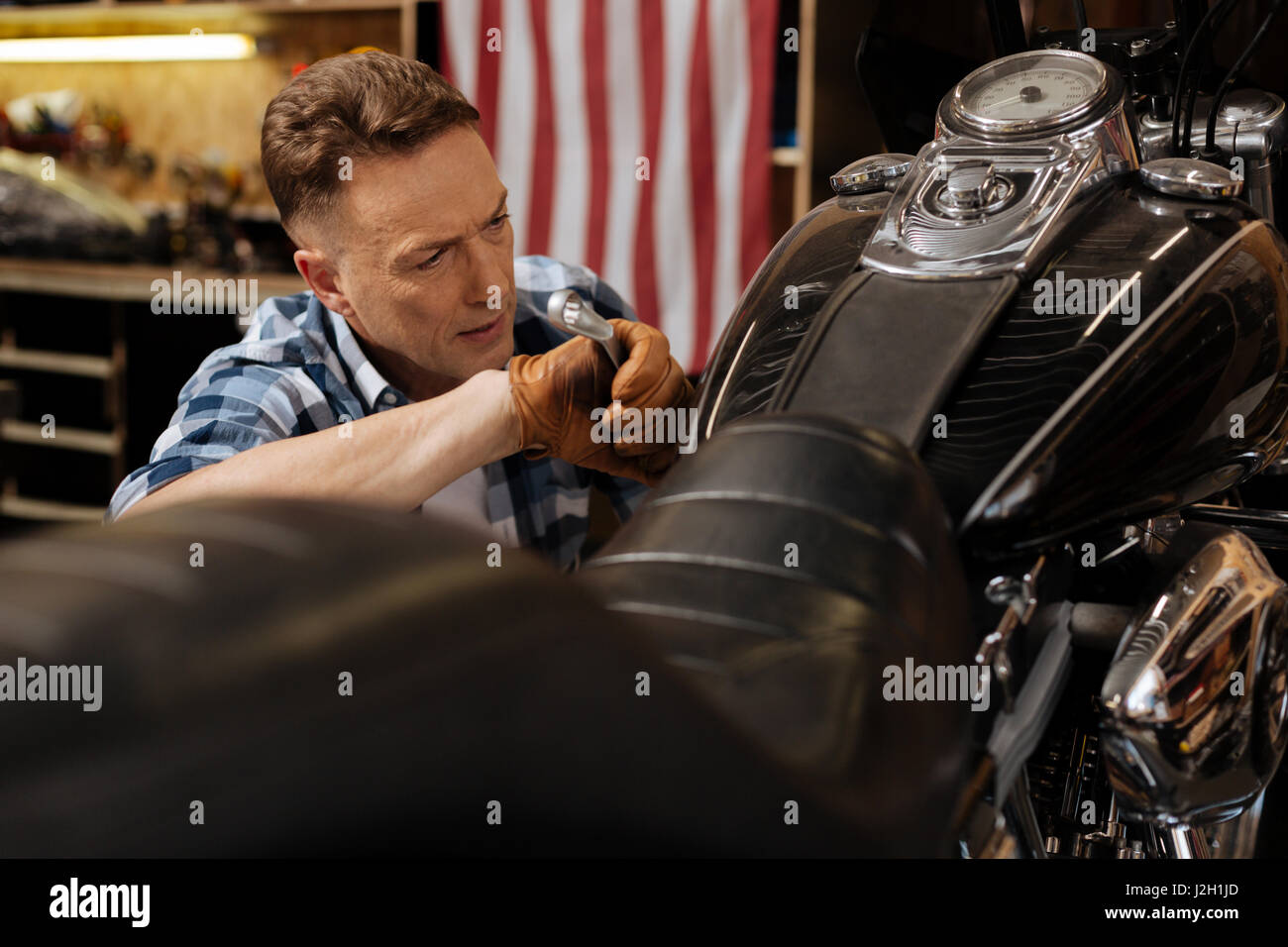 Precise good mechanic fixing the bolt - Stock Image