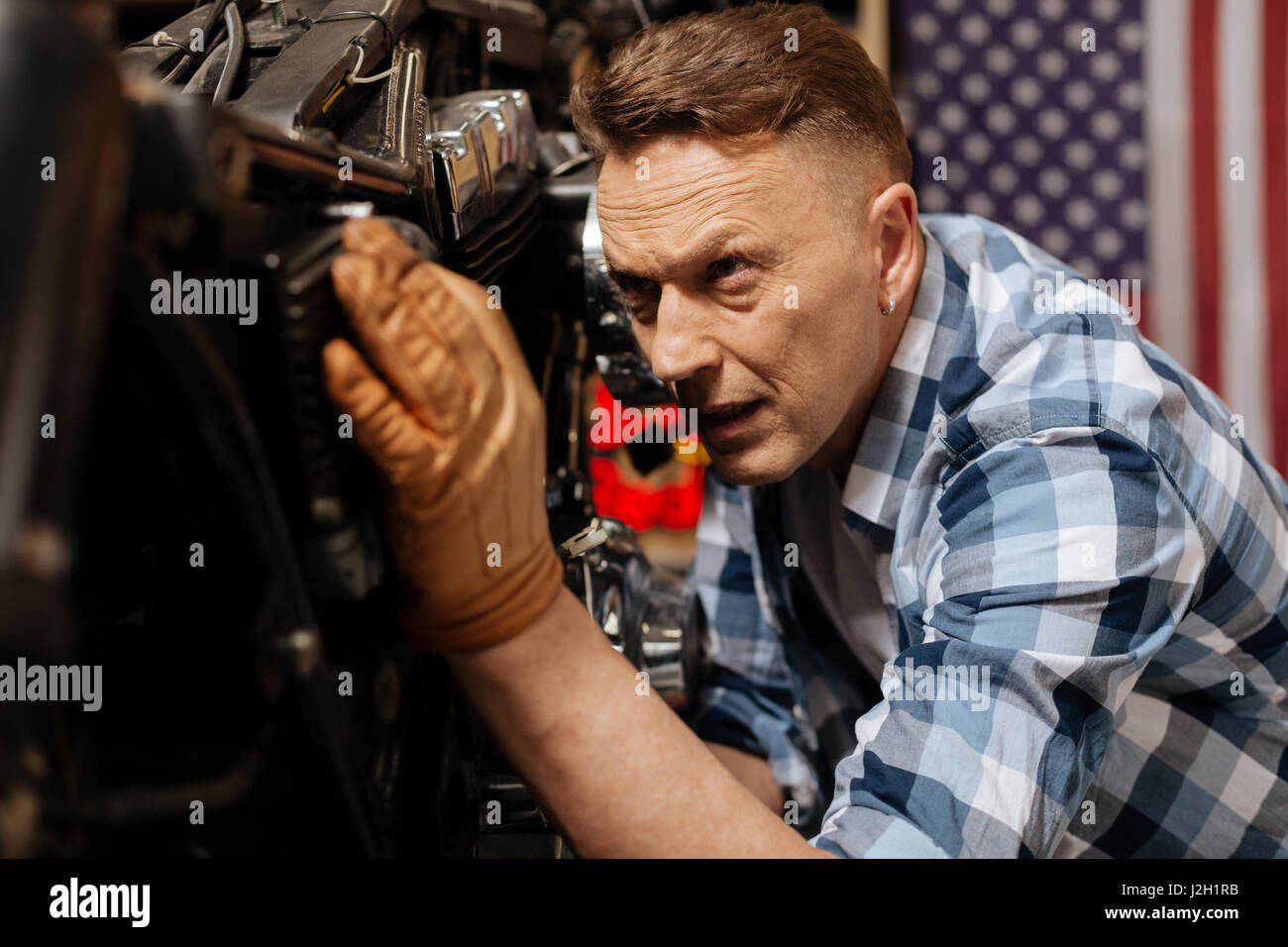 Scrupulous handsome mechanic doing a checkup - Stock Image