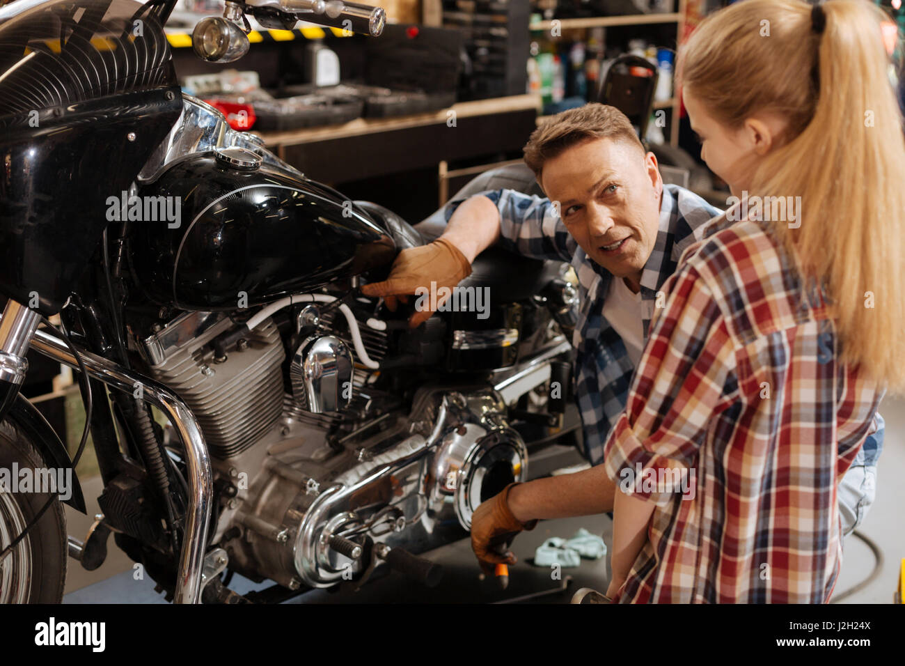 Dedicated skillful mechanic telling some interesting facts - Stock Image