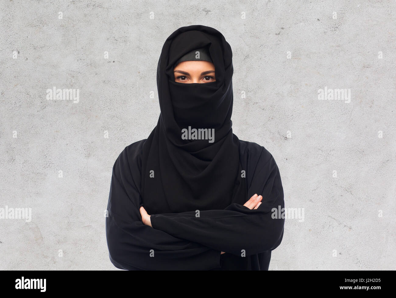 muslim woman in hijab over gray background - Stock Image