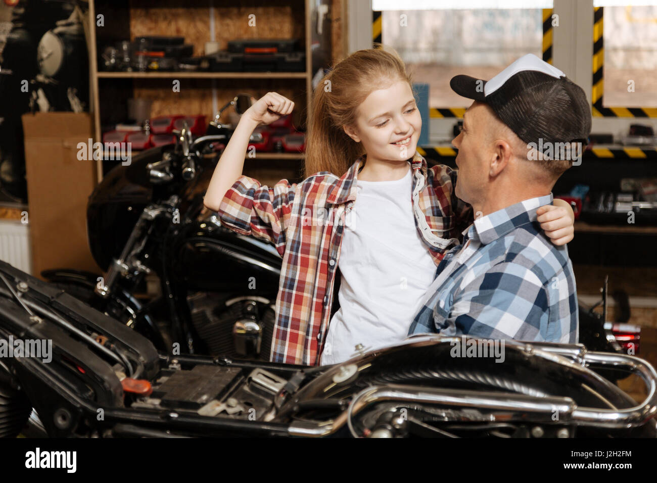 Cheerful sincere guy adoring his daughter - Stock Image