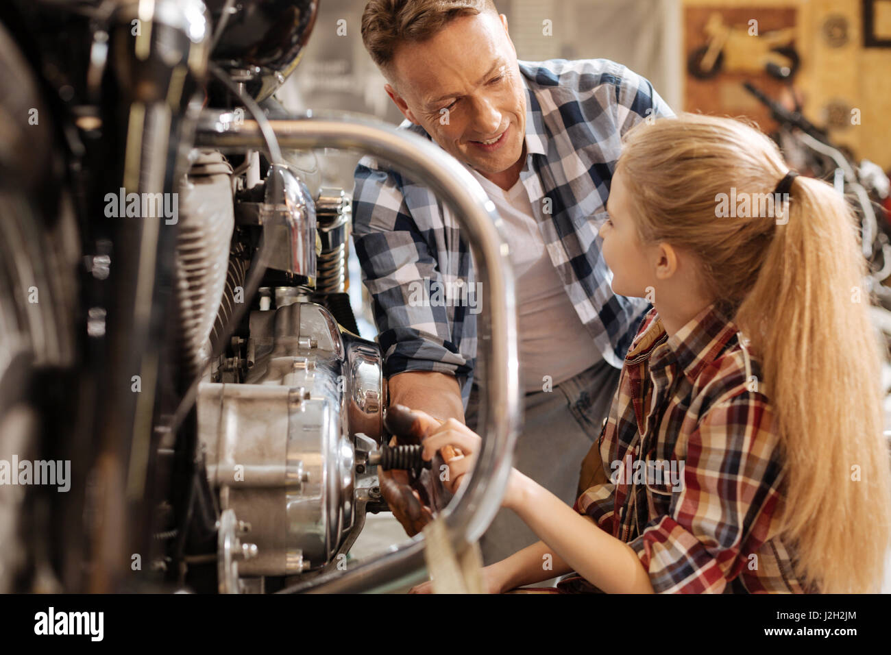 Capable mechanic telling daughter about mechanisms of the bike - Stock Image