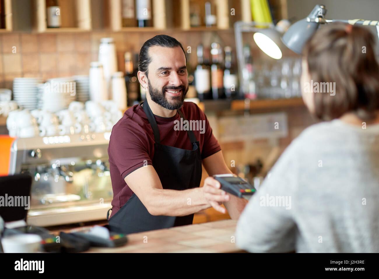 man or waiter with card reader and customer at bar Stock Photo