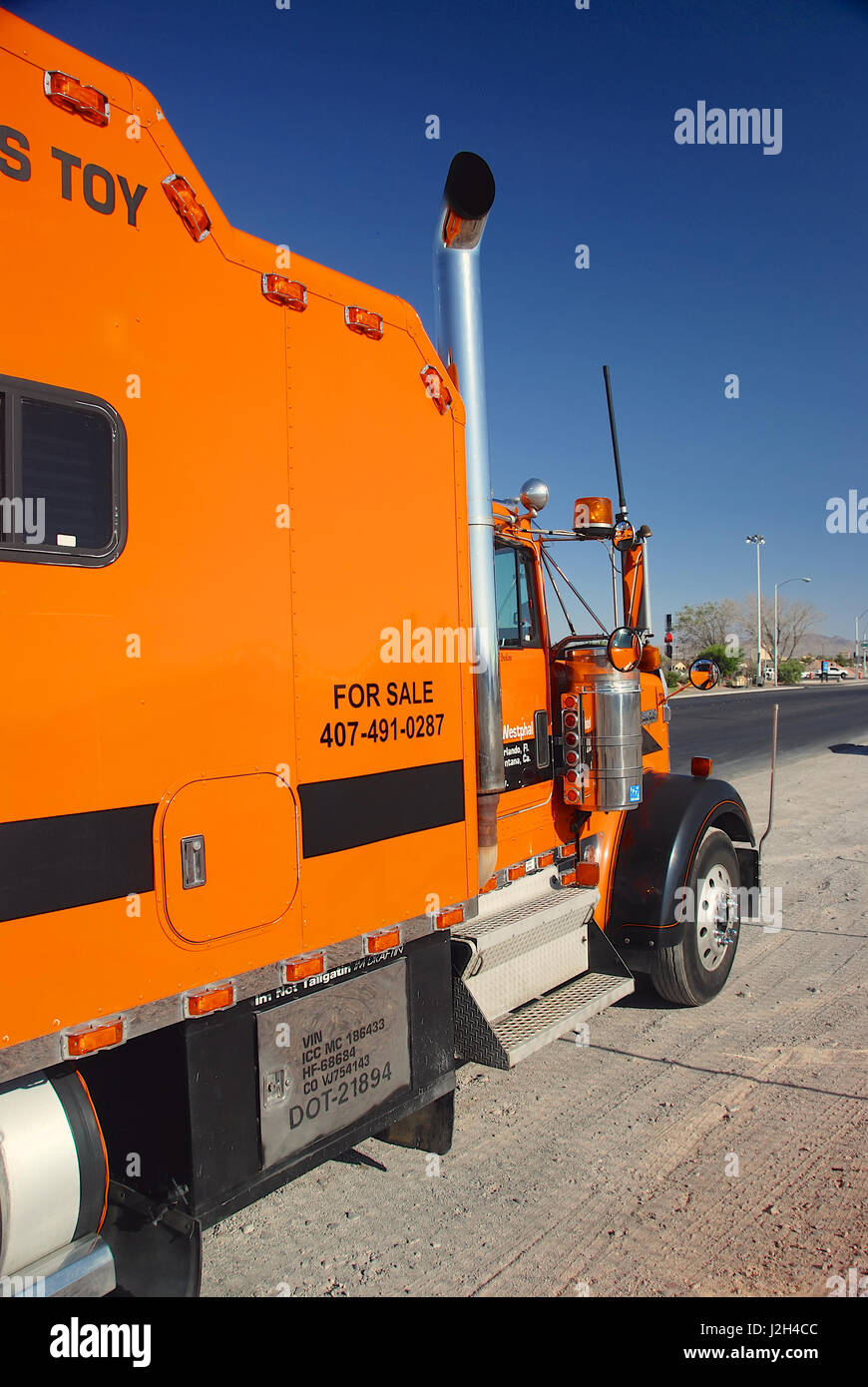 Orange Kenworth Truck parked by the side of the highway in Nevada, USA - Stock Image