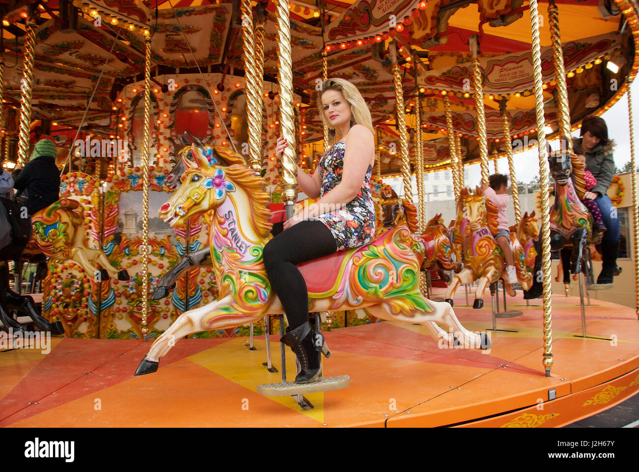 Beautiful blonde on a merry-go-round horse at a fun fair - Stock Image