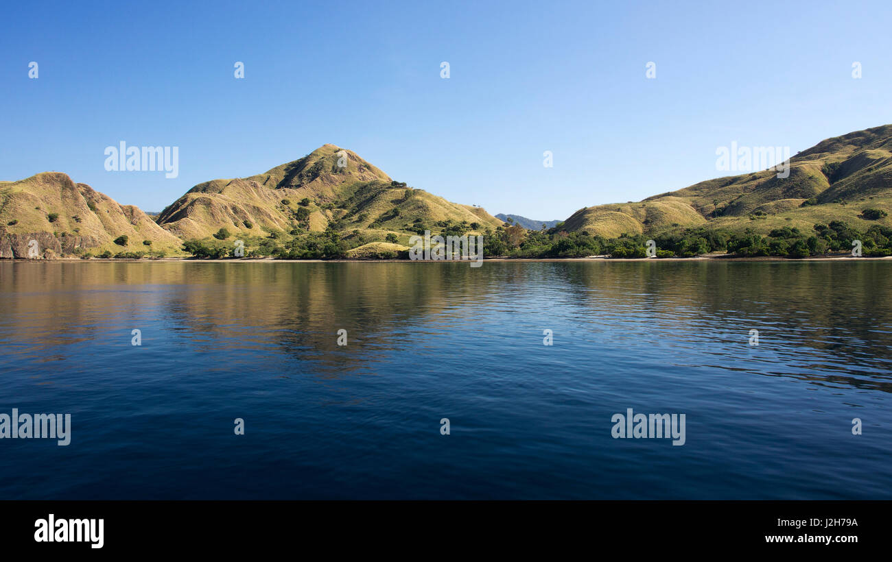 Coastline of mountains with green vegetation reflected  in blue ocean water at Labuan Bajo in Flores, Indonesia. - Stock Image