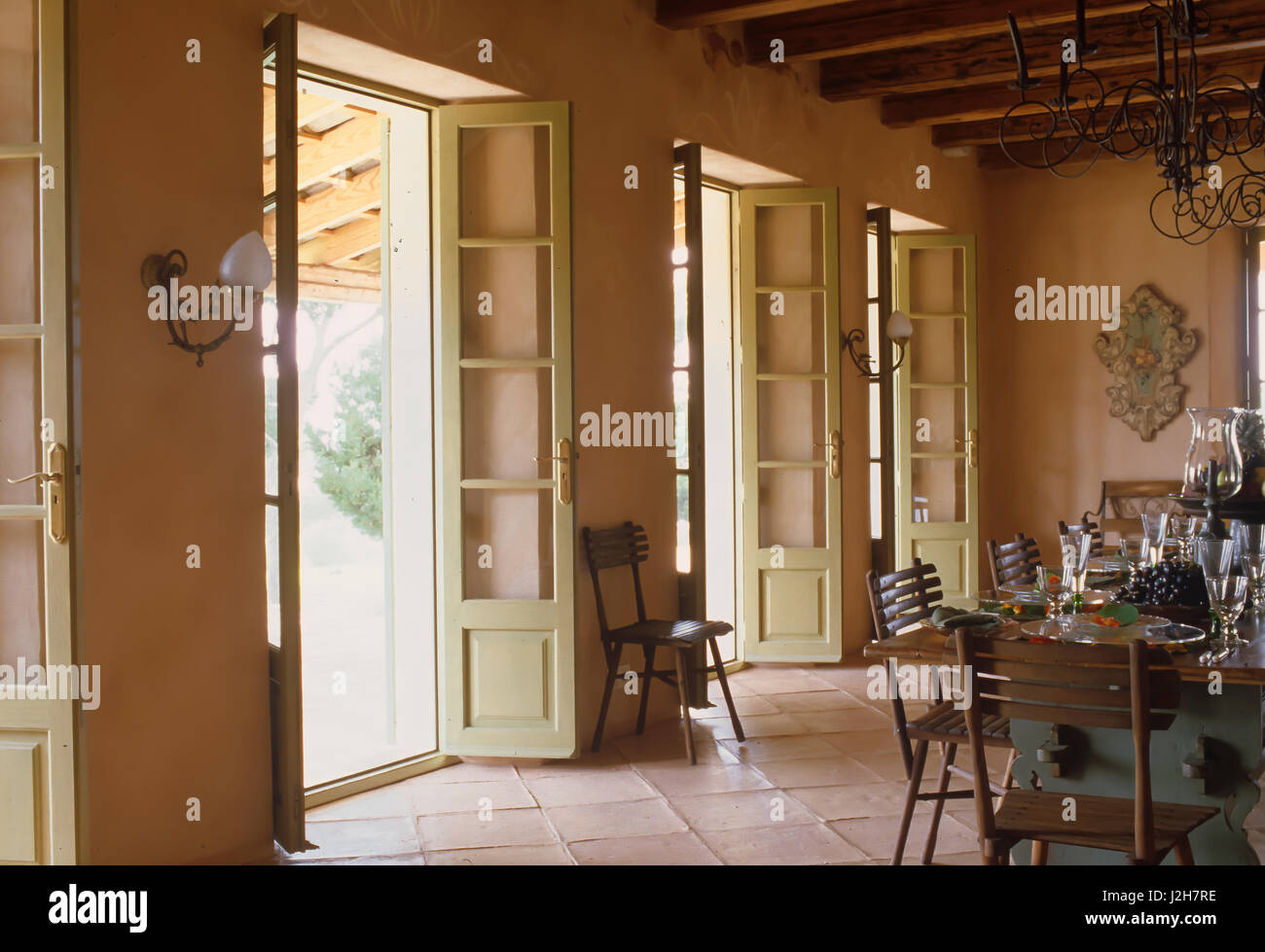 Table and chairs with open French doors - Stock Image