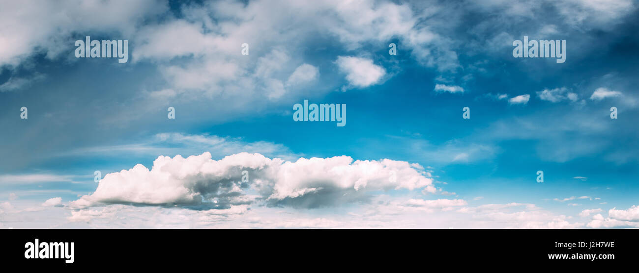 Panorama Of Bright Blue Sky With White Fluffy Clouds. Cloudy Sky. Blue Sunny Cloudscape Background - Stock Image