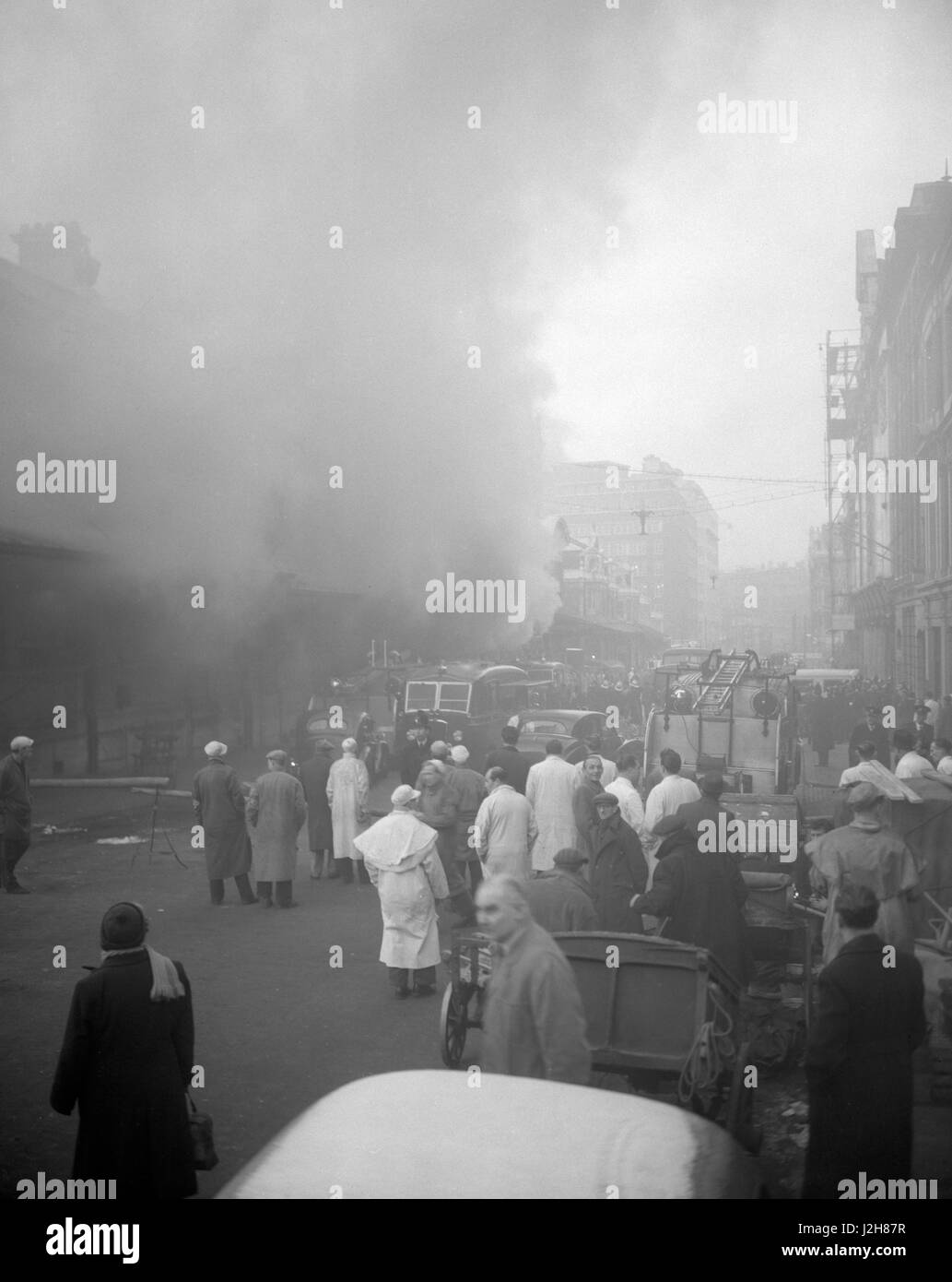 White-coated porters watch the fire in the basement  premises of the Union Cold Storage Company at Smithfield Market, - Stock Image