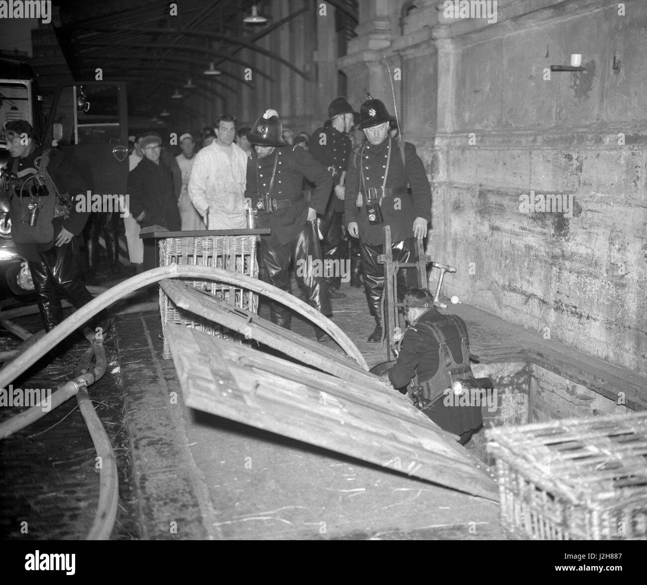 A fireman descends a ladder leading to the basement premises of the Union Cold Storage Company at Smithfield Market, - Stock Image