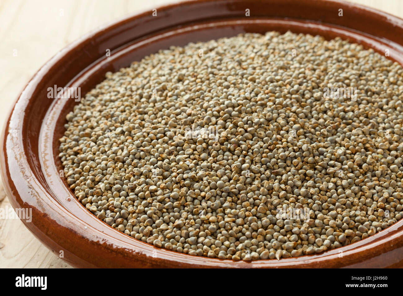 Dish with dried pearl millet close up - Stock Image