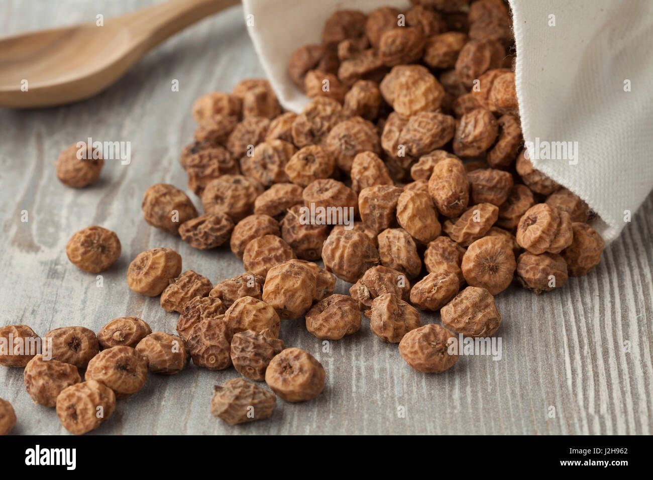 Sack with unshelled raw tiger nuts - Stock Image
