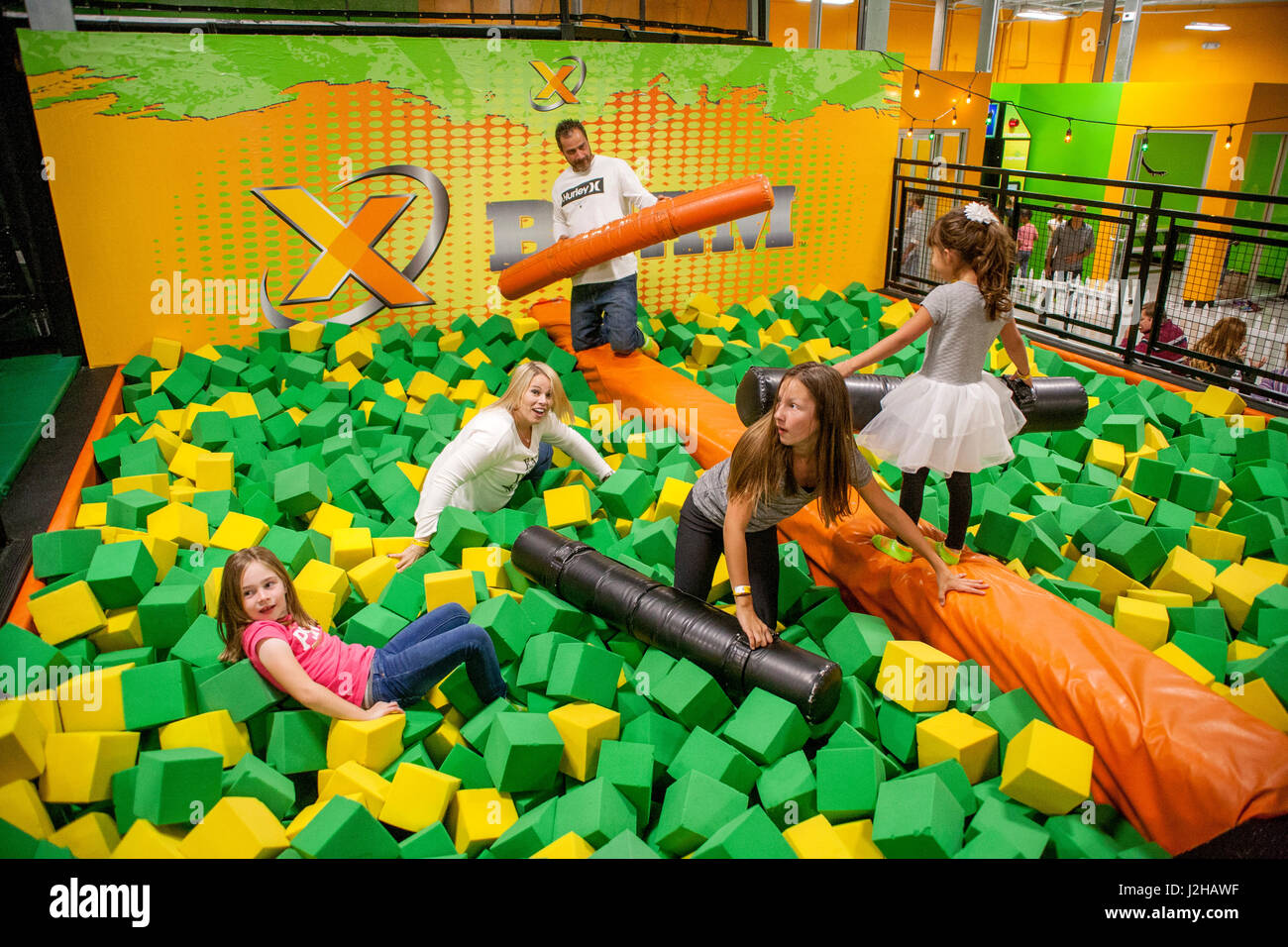 Children square off on the X-Beam balance attraction amid piles of foam rubber blocks at a Costa Mesa, CA, trampoline - Stock Image