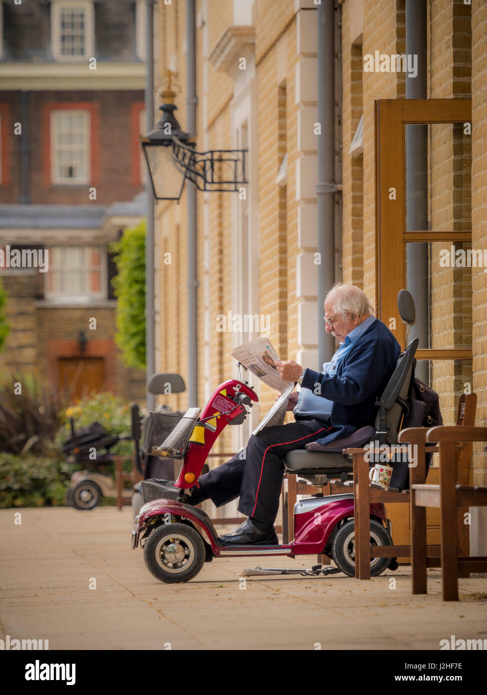 Chelsea Pensioner at Royal Hospital Chelsea, sat on mobility scooter outside apartment reading newspaper, London, - Stock Image