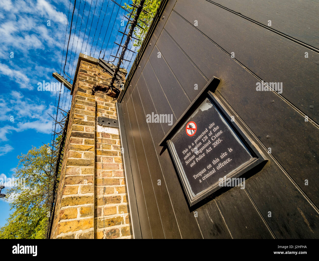 Warning sign and barriers along perimeter wall of buckingham Palace, London, UK. - Stock Image