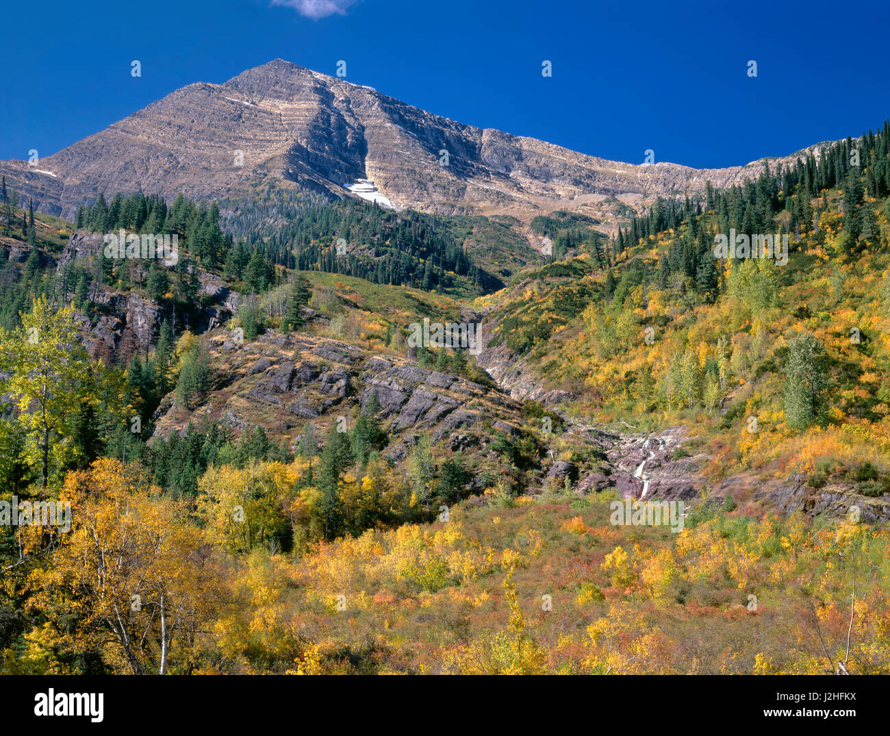 USA, Montana, Glacier National Park, Heavens Peak rises above fall-colored slopes and small waterfall, view from - Stock Image