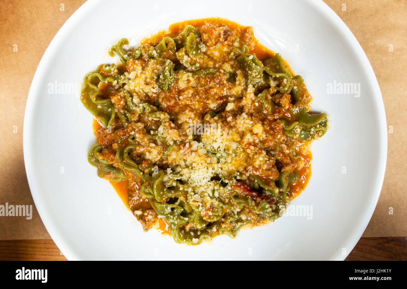 Mafaldine spinach pasta with a savory meat ragù and Parmesan cheese - Stock Image