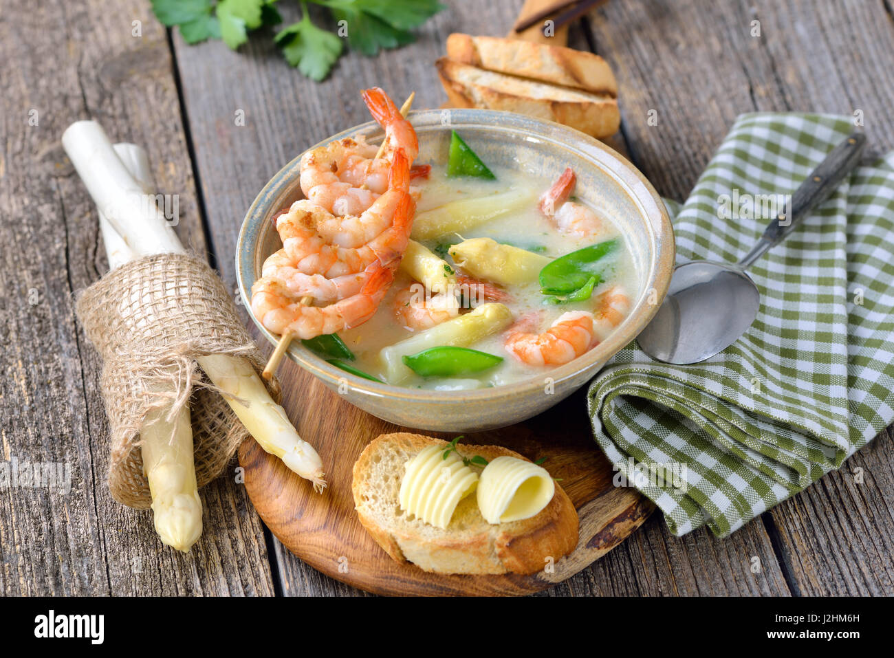 Cream of asparagus soup with fried prawns and snow peas, served with toasted baguette with butter rolls - Stock Image