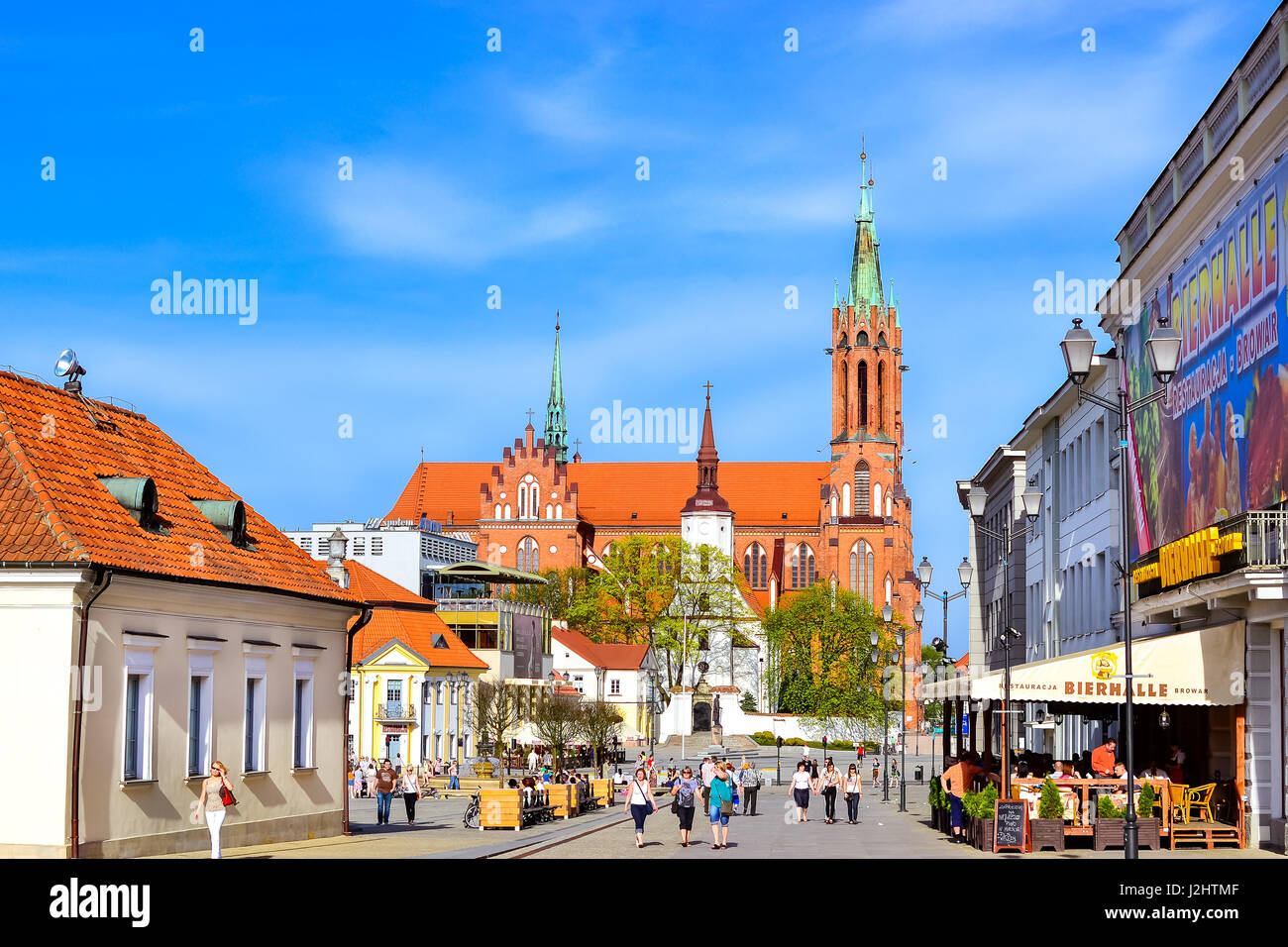 Bialystok, Poland - April 29, 2012: Tourists walk in sunny summer day on pavers central square of Kosciusko Market. - Stock Image