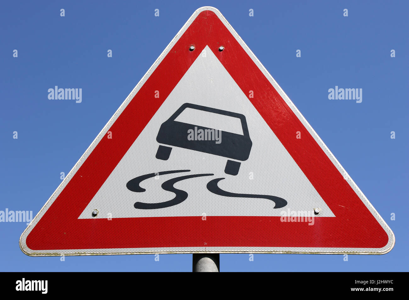 German road sign: slippery road - Stock Image