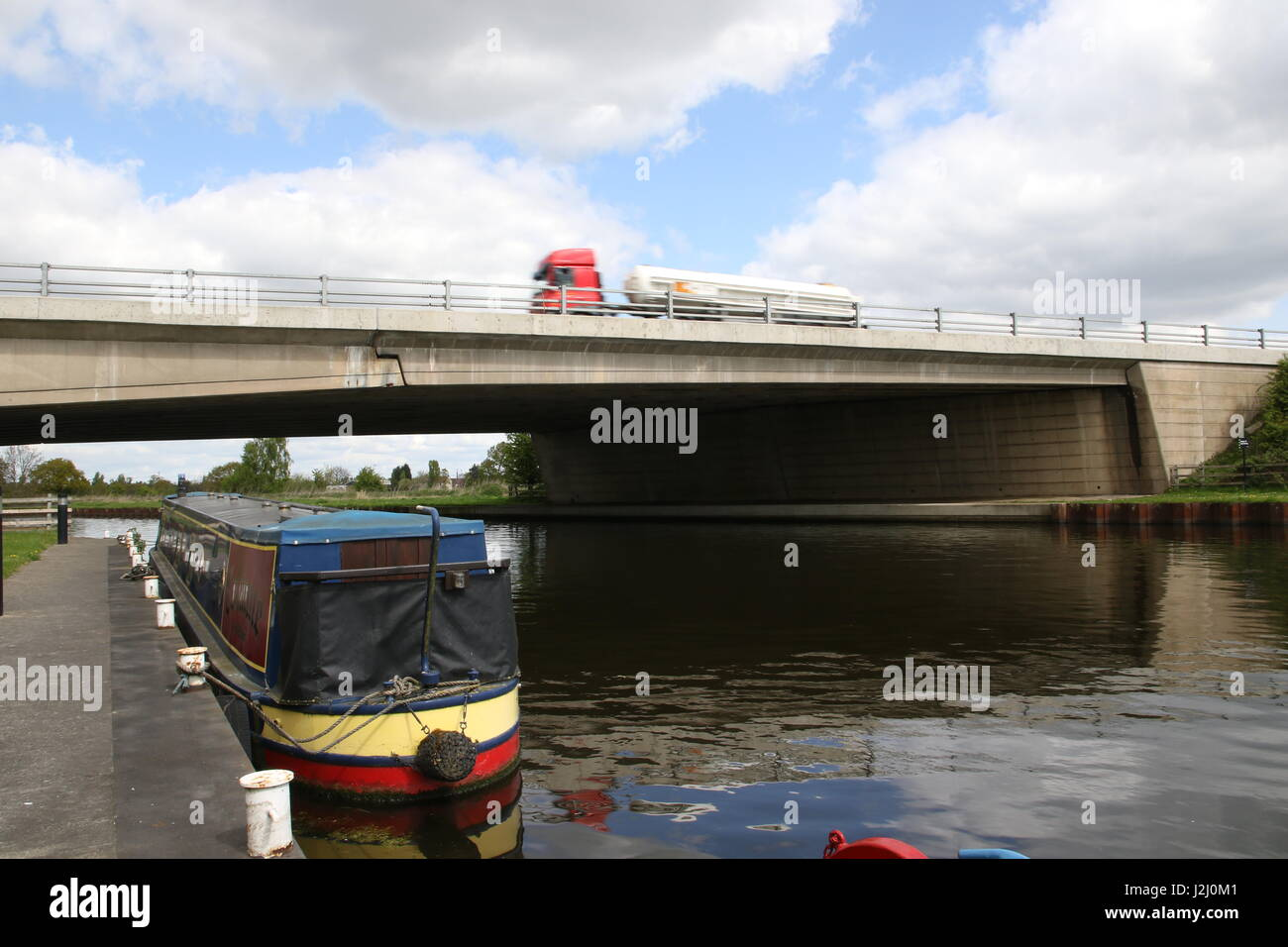 A lorry passes over a motorway bridge crossing the Aire Calder Navigation Canal with a barge moored along the towpath - Stock Image