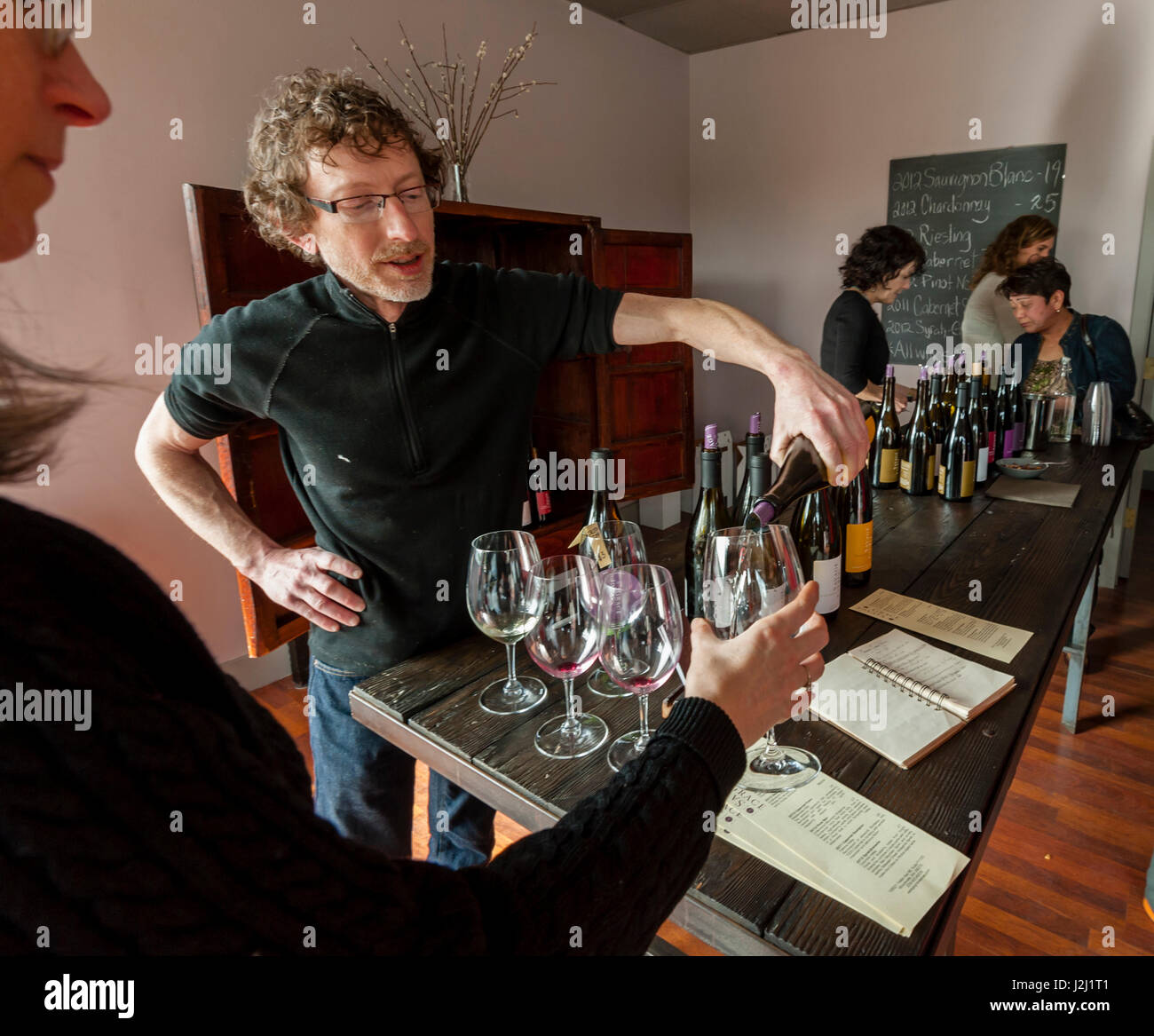 Usa, Washington State, Woodinville. Winemaker Michael Savage of Savage Grace winery pours for a guest. - Stock Image