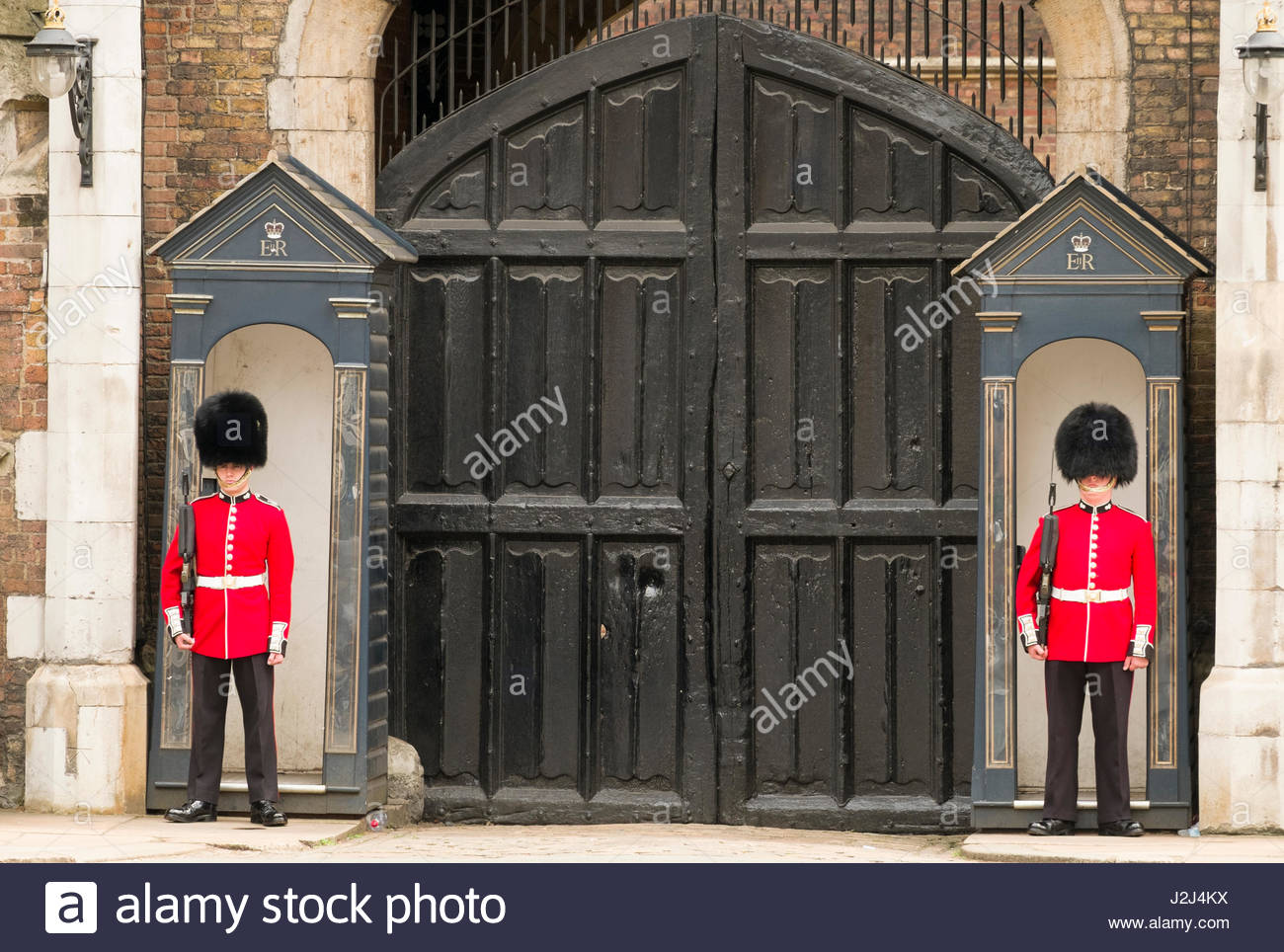 Grenadier Guards standing at attention holding L85A1 IW bullpup rifles on sentry duty, St James's Palace, Cleveland - Stock Image