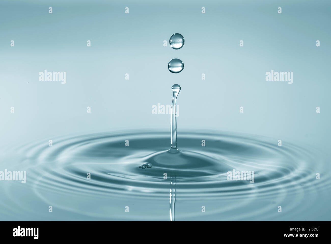Water droplet on water surface. - Stock Image