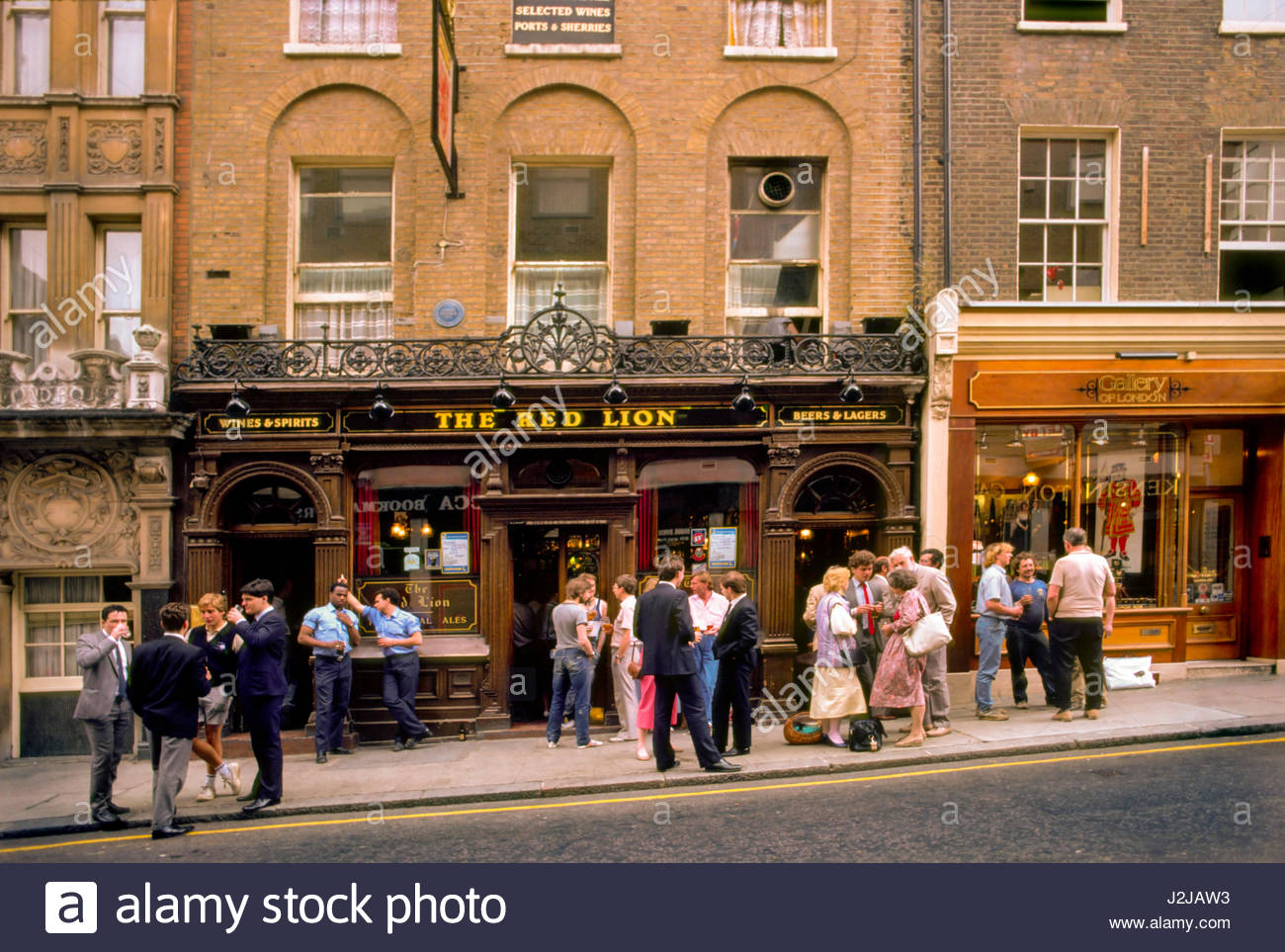 Duke of York, St. James's, London, England, United Kingdom. People outside the Red Lion Pub at lunch time drinking - Stock Image
