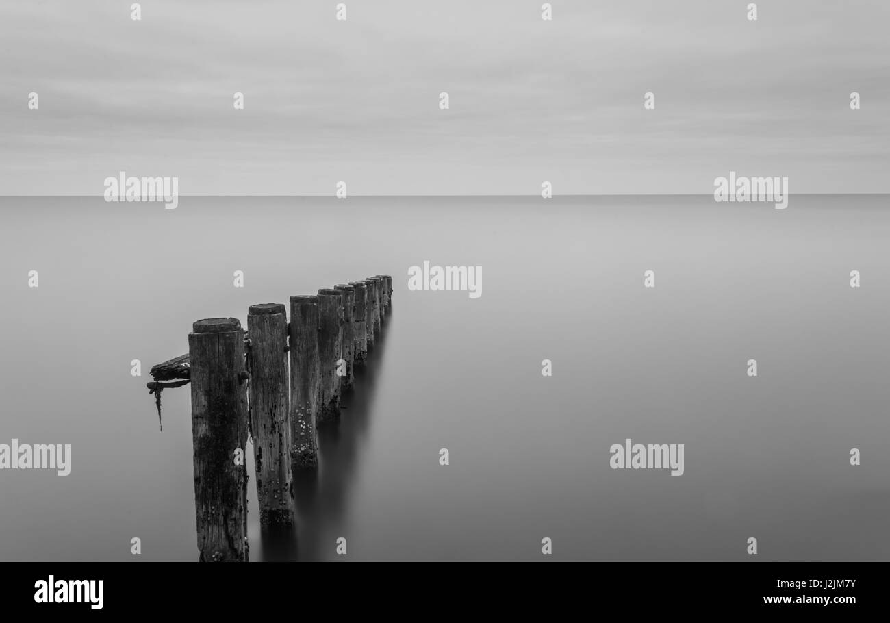 Wooden construction in sea.black and white ,long exposure.Barton on Sea Uk England. - Stock Image