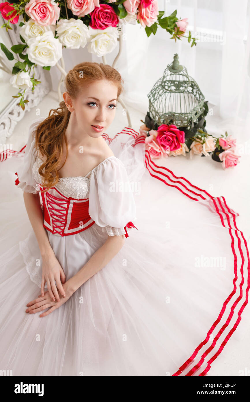 b18dc63c9bfc Cute ballerina in stage costumes and bouquets of spring flowers. Retro dress.  She sits on the floor.