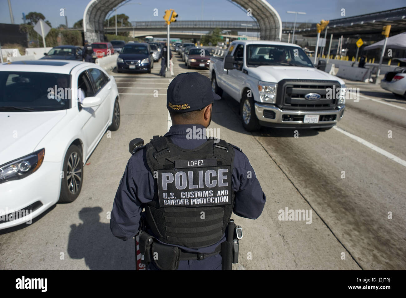 An agent of the US Customs and Border Protection Office (CBP) appears among the traffic that directs from the United - Stock Image