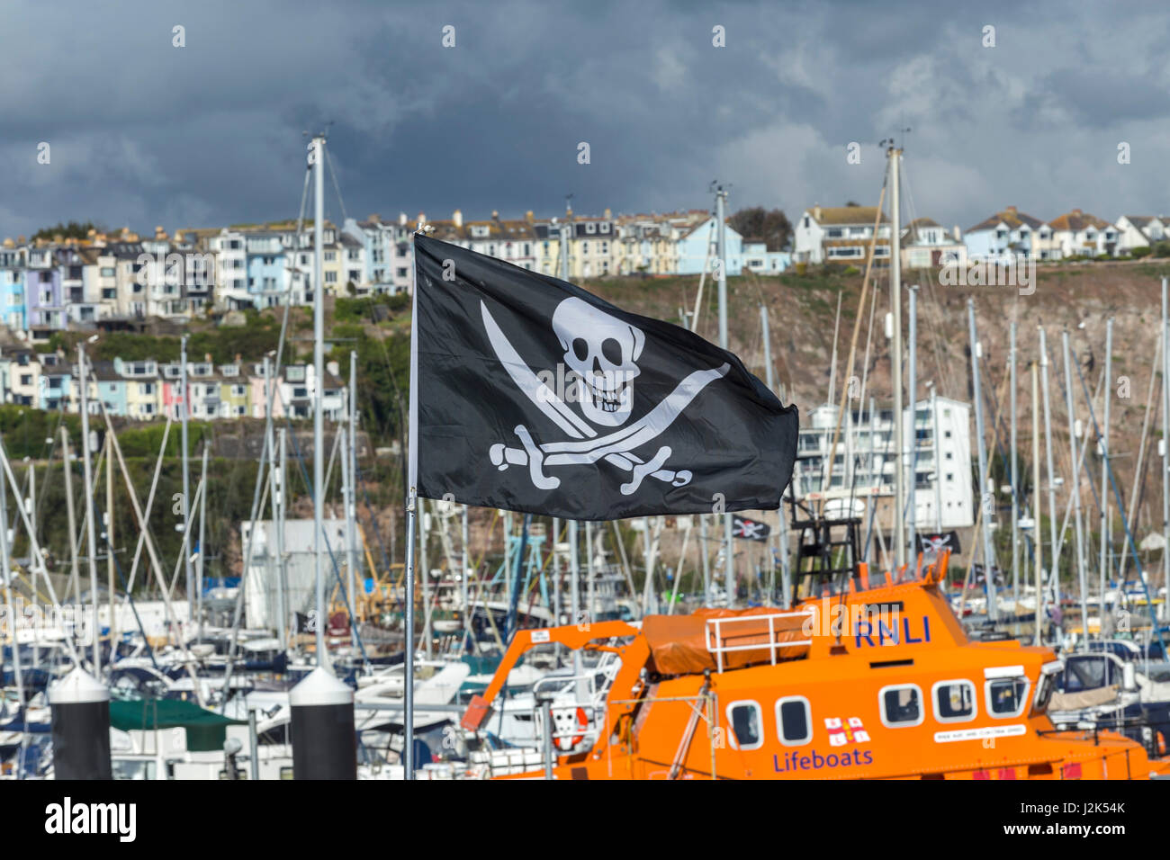 Brixham, Devon, 29th Apr 17 A skull and crossbones flies beside the Torbay Lifeboat at the 8th Brixham Pirate Festival.The - Stock Image