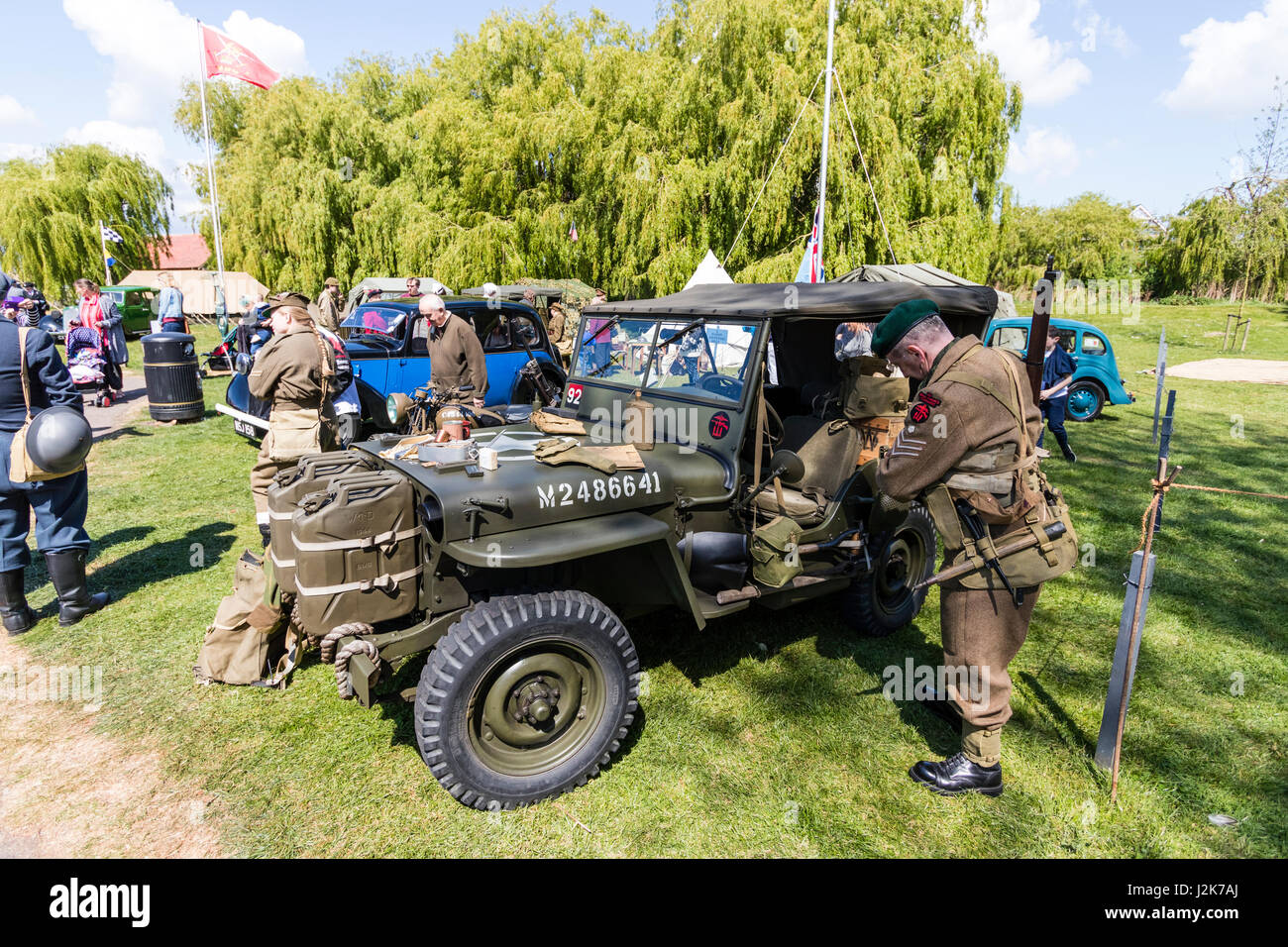 Salute to the 40s re-enactment event. Various vehicles tents and displays on grass area with people wandering around looking and chatting. & Salute to the 40s re-enactment event. Various vehicles tents and ...