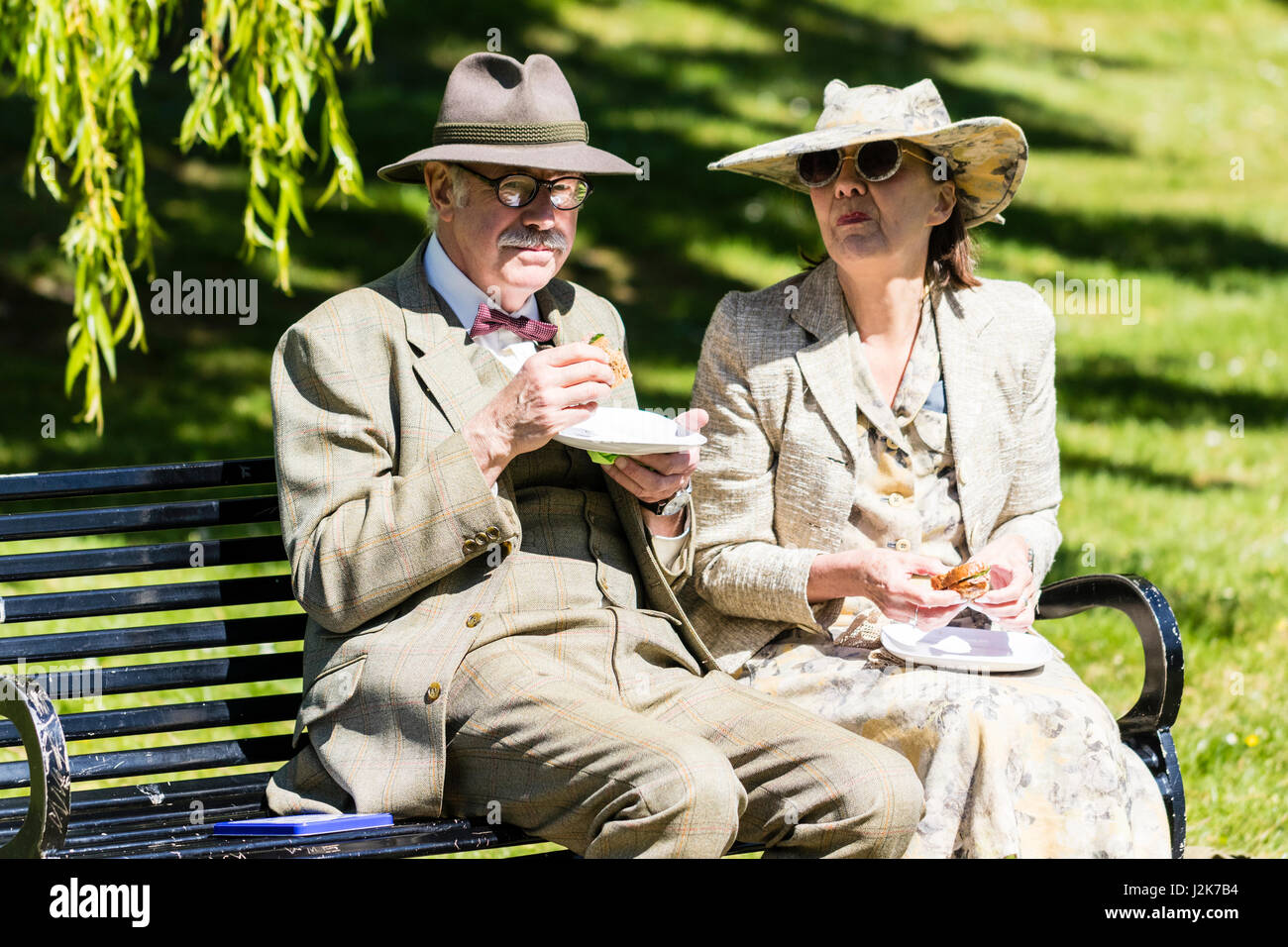 Salute to the 40s event. A senior couple on a park bench pause their Sandwiches to pose for a picture. Both dressed - Stock Image