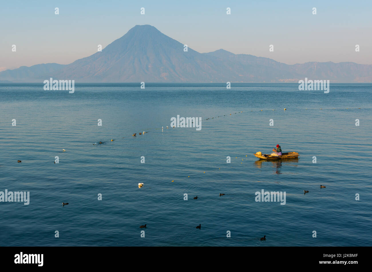 Fisherman in his boat controlling his nets in the blue waters of the Atitlan lake with a volcano in the background - Stock Image