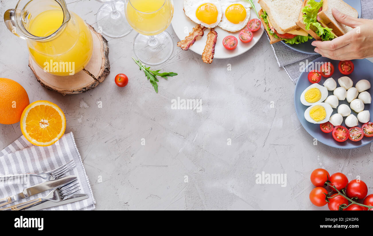 Breakfast table with fried eggs, bacon, cherry tomatoes, sanwiches, orange juice Stock Photo