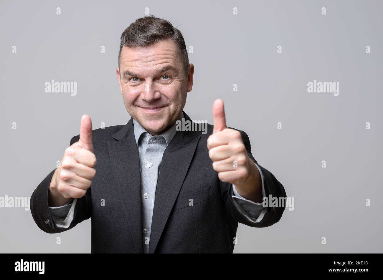 Grinning man in dark suit jacket with two thumbs up over gray background. Includes copy space. - Stock Image