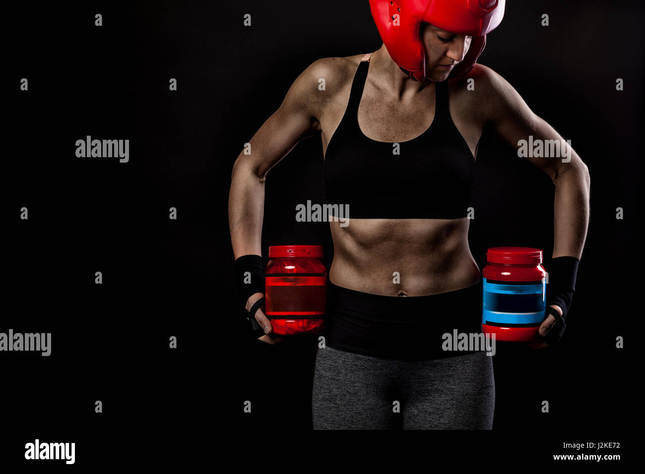 Female athlete with bodybuilding supplements and proteins - Stock Image
