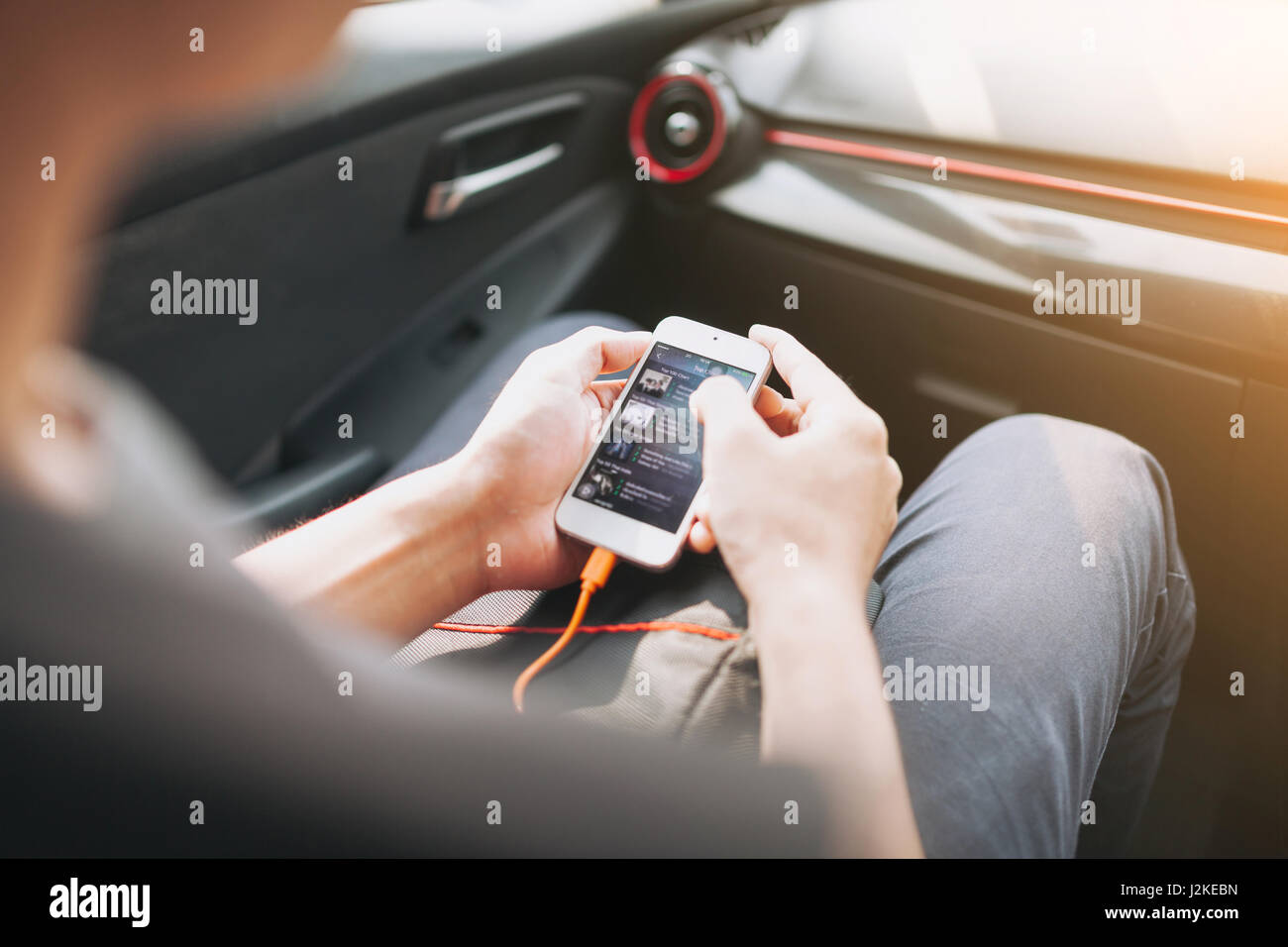 Man connecting phone to the car media system. - Stock Image