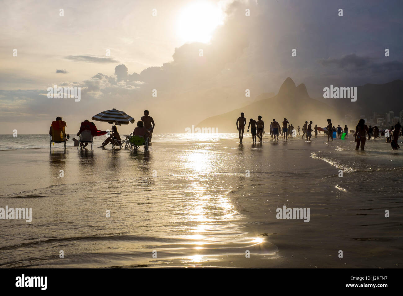 RIO DE JANEIRO - JANUARY 16, 2017: Visitors enjoy the last of the afternoon sun as the tide sweeps onto a sunset - Stock Image