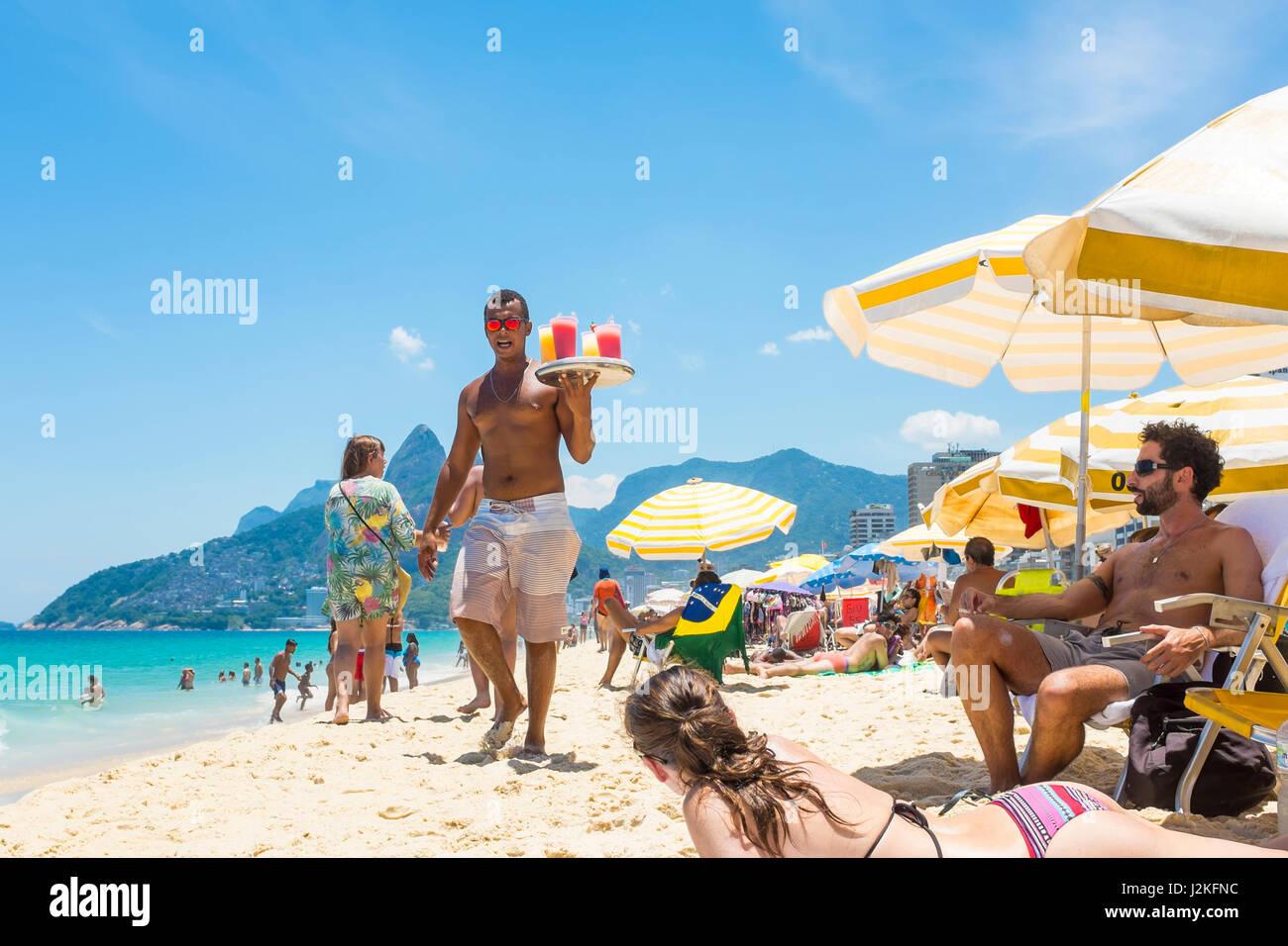 RIO DE JANEIRO - JANUARY 24, 2017: Young Brazilian beach vendor carries a tray of caipirinha cocktails in the midday - Stock Image