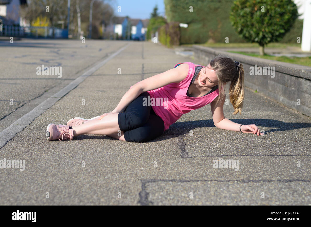 Female athlete with calf cramps lying on the sidewalk of a tarred road clutching her lower leg muscles in agony - Stock Image