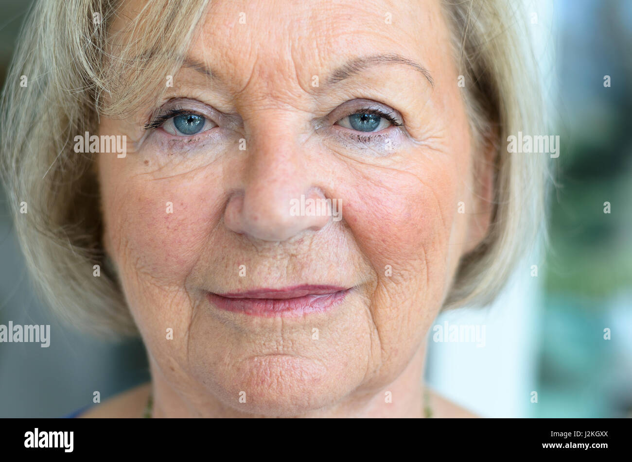 Close up cropped view of the face of an attractive senior woman with fair hair, blue eyes and wrinkled skin looking - Stock Image