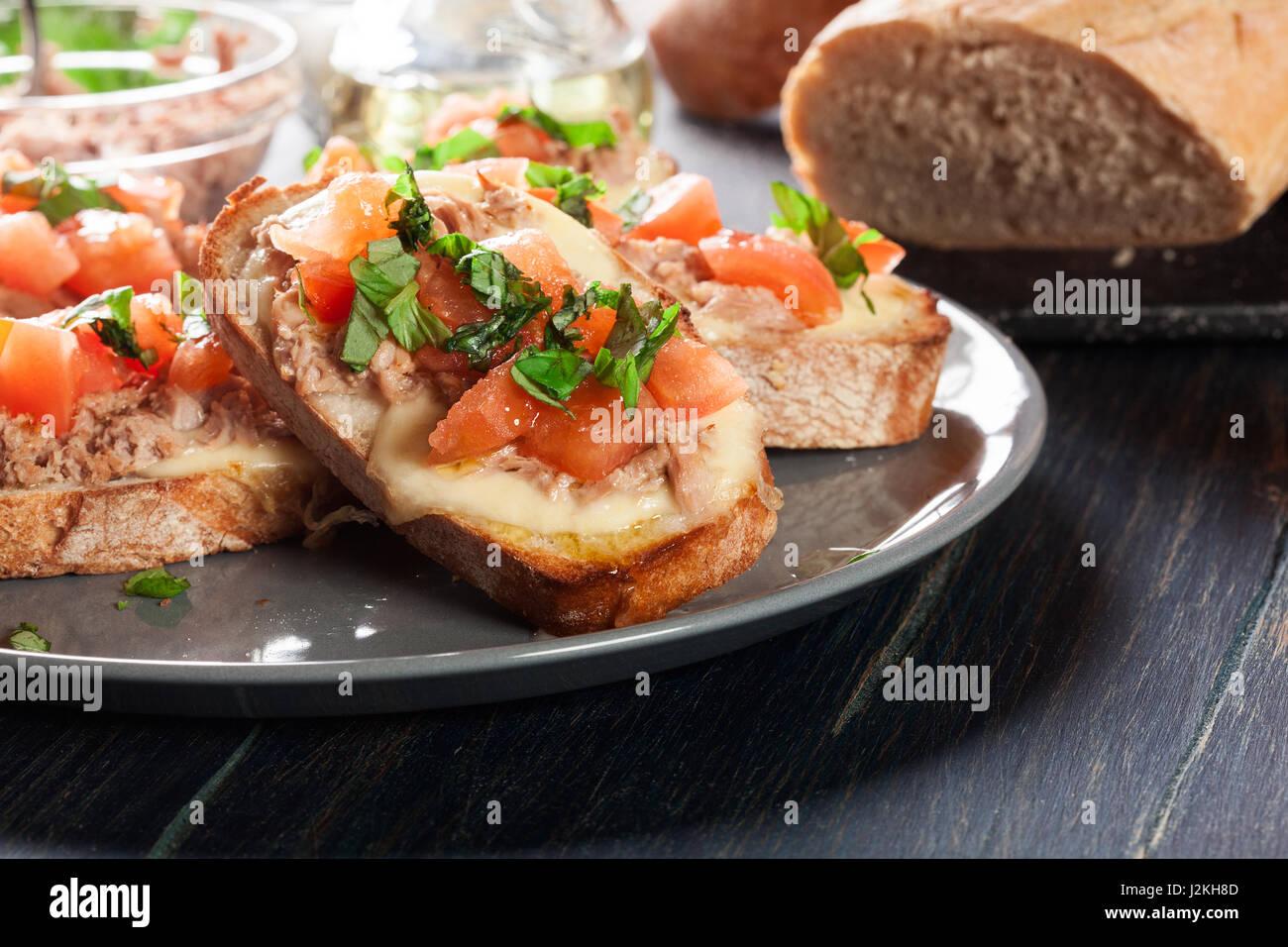 Appetizer bruschetta with tuna, mozarella cheese and tomatoes. Italian cuisine - Stock Image